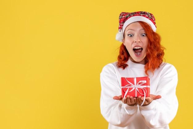 노란색 벽에 작은 크리스마스 선물을 가진 젊은 여자의 전면보기