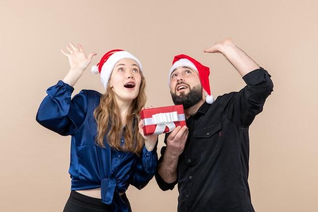 분홍색 벽에 그녀에게 선물을 들고 남자와 젊은 여자의 전면보기