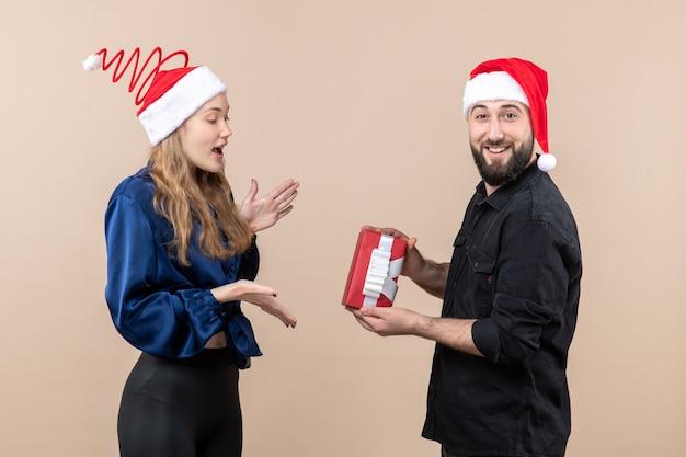 Вид спереди молодой женщины с мужчиной, который делает ей подарок на розовой стене