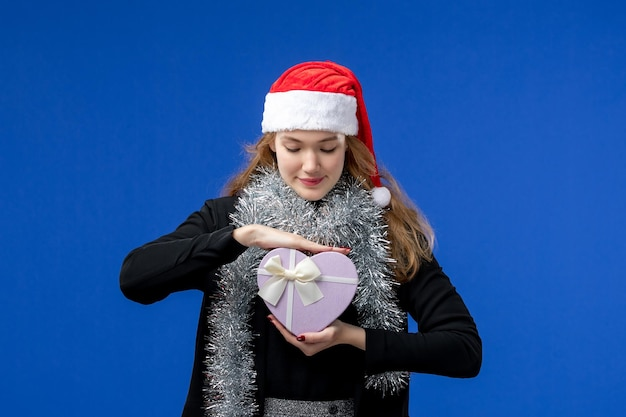 파란 벽에 새해 선물을 들고 있는 젊은 여성의 전면 모습