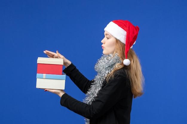 青い壁に新年のプレゼントと若い女性の正面図