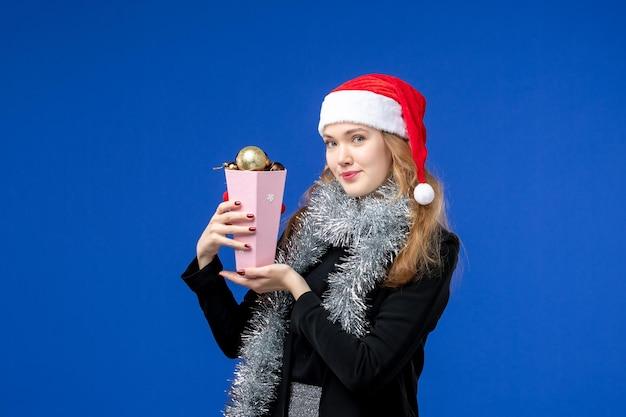 青い壁に新年の木のおもちゃを持つ若い女性の正面図