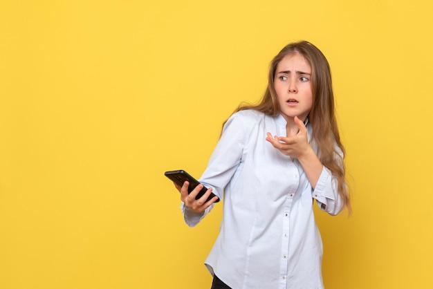 노란색 벽에 전화를 가진 젊은 여자의 전면보기