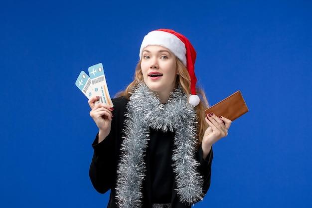 青い壁に飛行機のチケットを持つ若い女性の正面図