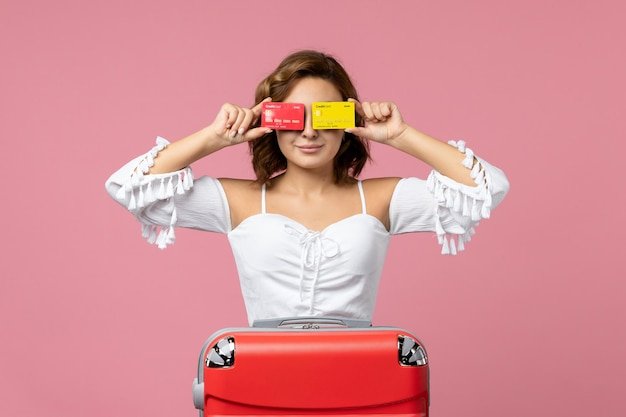 ピンクの壁に銀行カードを保持している赤い休暇バッグを持つ若い女性の正面図