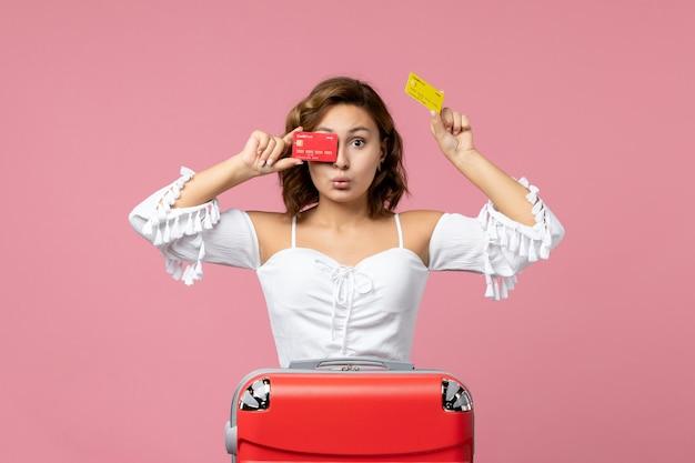 Вид спереди молодой женщины с красной туристической сумкой, держащей банковские карты на розовой стене