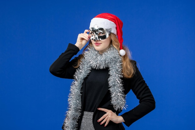 青い壁に銀のマスクを持つ若い女性の正面図