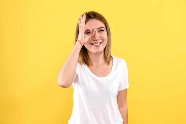 Вид спереди молодой женщины с улыбкой на желтой стене