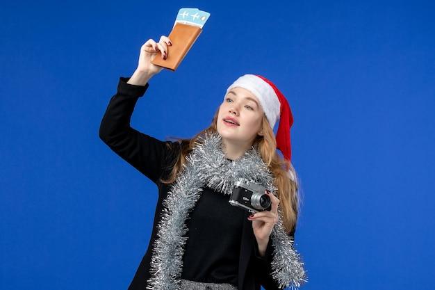 파란 벽에 티켓과 카메라를 들고 있는 젊은 여성의 전면 모습