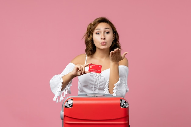 ピンクの壁に銀行カードを保持している休暇バッグを持つ若い女性の正面図