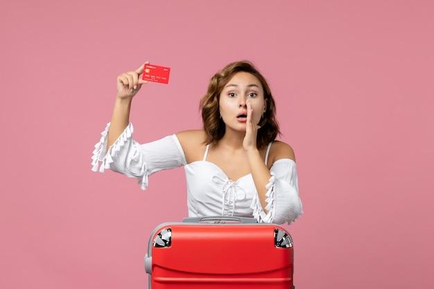 Вид спереди молодой женщины с туристической сумкой, держащей банковскую карту на розовой стене