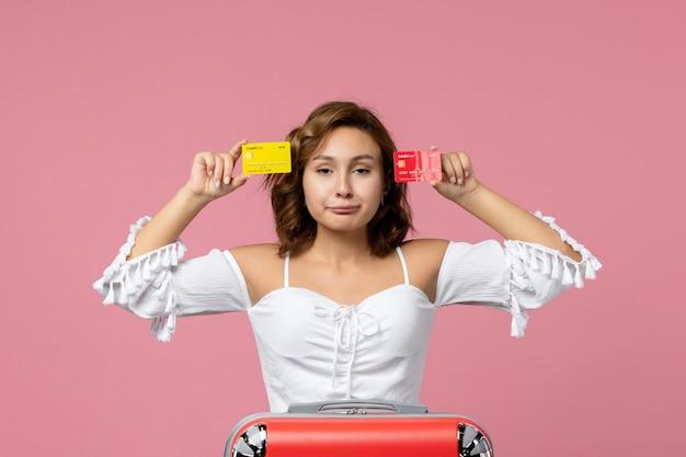 분홍색 벽에 은행 카드를 들고 휴가 가방을 들고 있는 젊은 여성의 전면