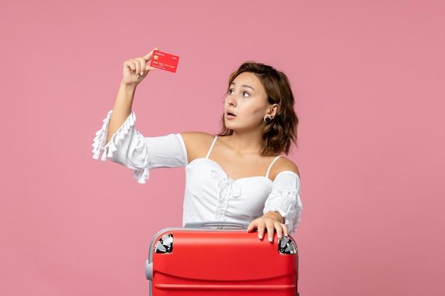 ピンクの壁に赤い銀行カードを保持している休暇バッグを持つ若い女性の正面図