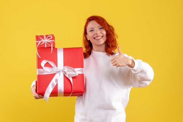 Вид спереди молодой женщины с рождественскими подарками на желтой стене
