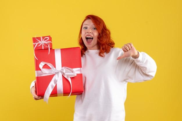크리스마스와 젊은 여자의 전면보기 노란색 벽에 선물