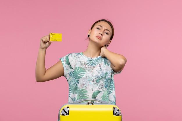 淡いピンクの壁に黄色の銀行カードとバッグを持つ若い女性の正面図