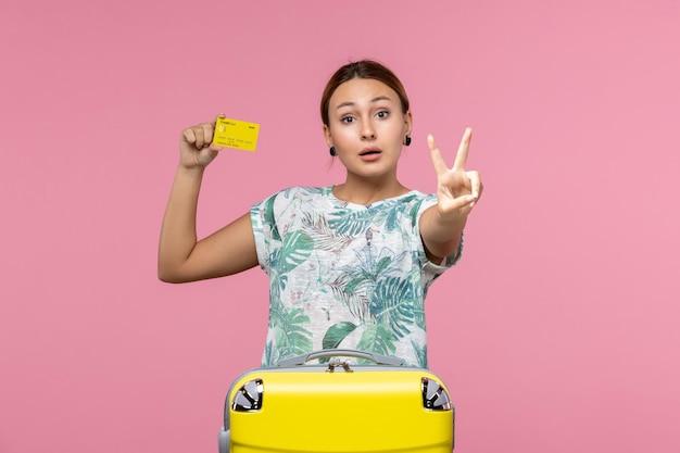 분홍색 벽에 노란색 은행 카드와 가방을 든 젊은 여성의 전면