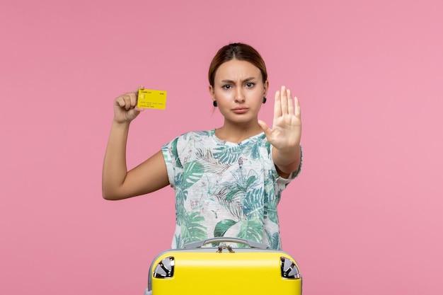 ピンクの壁に黄色の銀行カードと休暇バッグを持つ若い女性の正面図