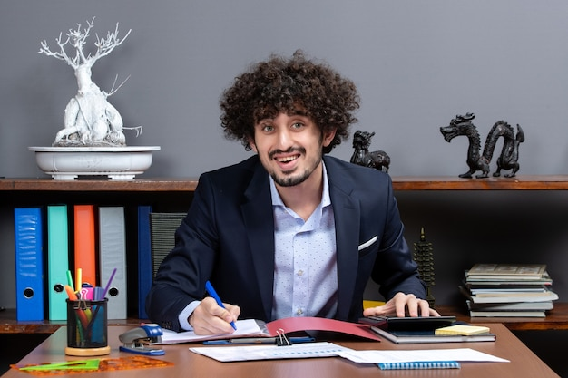 オフィスで何かを書く机に座っている若い労働者の正面図