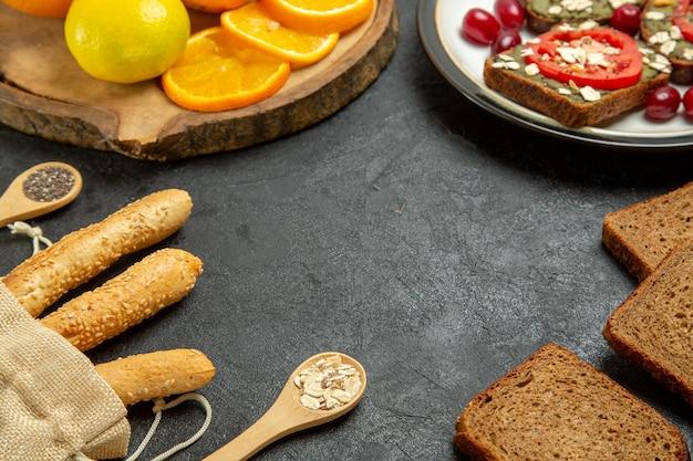 회색 표면에 신선한 오렌지와 함께 맛있는 아보카도 샌드위치의 전면보기