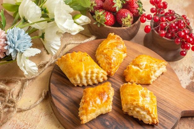木製の表面に果物とおいしいナッツペストリーの正面図