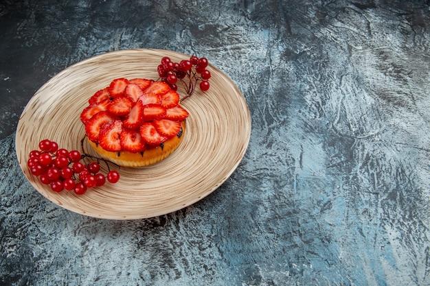 暗い表面に赤いベリーとおいしいストロベリーケーキの正面図