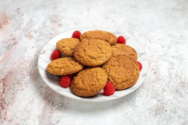 흰색 표면에 접시 안에 맛있는 설탕 쿠키의 전면보기