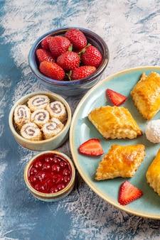 青い表面にフルーツとナッツのおいしい甘いケーキの正面図