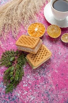 Вид спереди вкусного вафельного печенья с чашкой чая