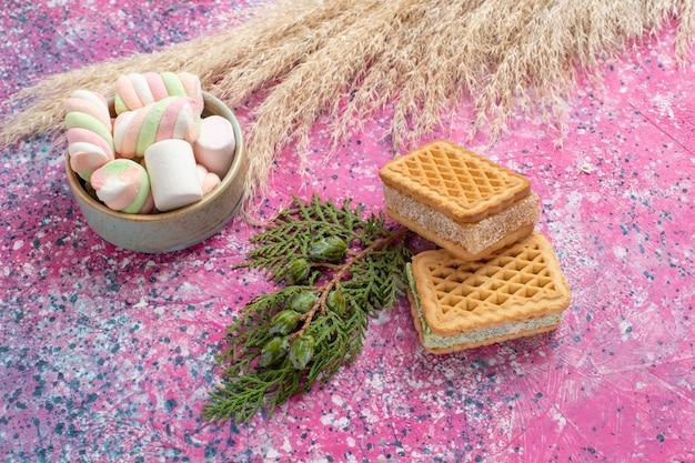 ピンクの机の上にマーシャローとおいしいワッフルクッキーの正面図