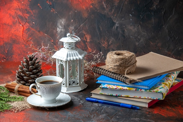 Front view of office suppliances and pen cinnamon limes conifer cone and a cup of tea a ball of rope on dark background