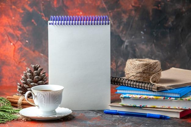 Vista frontale di forniture per ufficio e penna cannella lime cono di conifere e una tazza di tè su asciugamano marrone su sfondo scuro