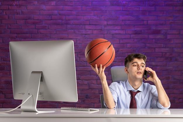 Офисный работник вид спереди за офисным столом держит баскетбол и разговаривает по телефону