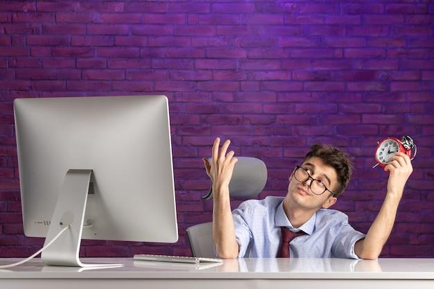 Офисный работник вид спереди за офисным столом, держа часы
