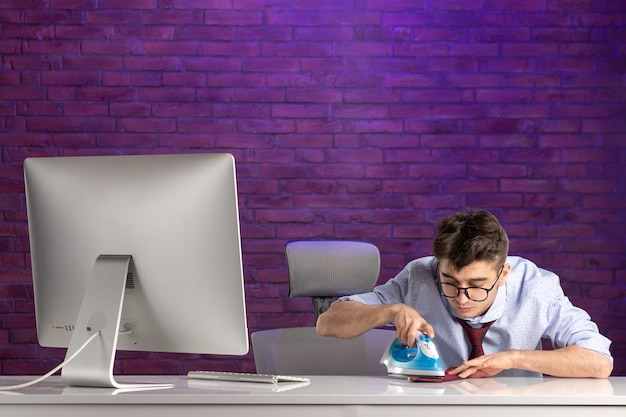 彼のネクタイをアイロンをかけているオフィスの机の後ろの正面のサラリーマン