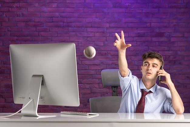 야구 공을 던지고 전화로 이야기 사무실 책상 뒤에 전면보기 회사원
