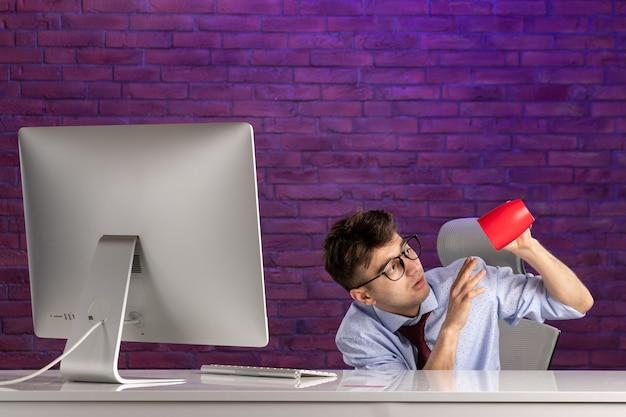 赤いカップとオフィスデスクの後ろの正面のサラリーマン