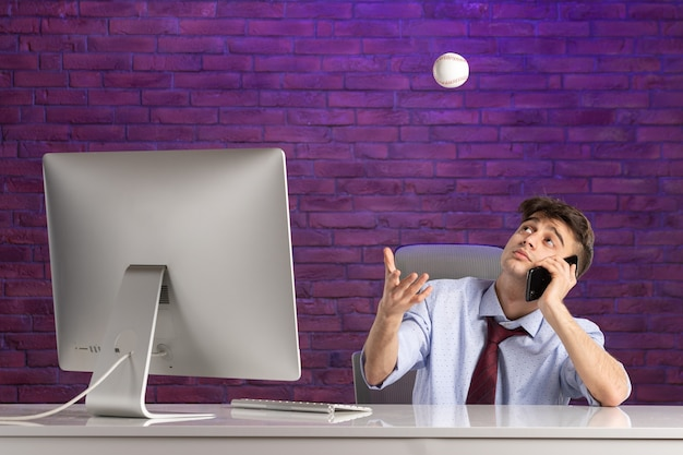 Front view office worker behind office desk holding baseball ball and talking at phone