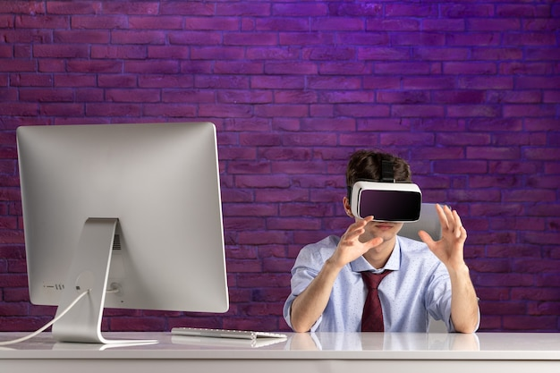 Front view office worker behind office desk playing virtual reality