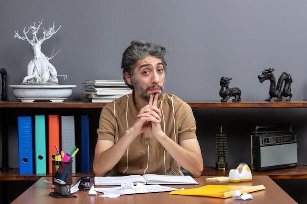 自分の机に座って考えている正面のサラリーマン