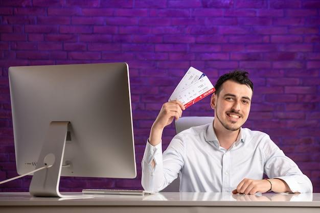 職場の後ろに座って飛行機のチケットを持っている正面図のサラリーマン