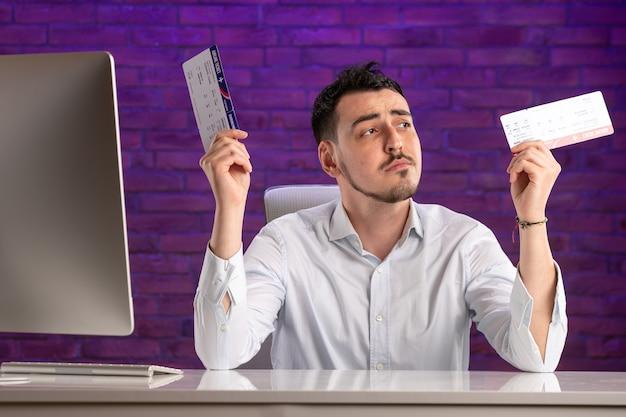 그의 작업 장소 뒤에 앉아 티켓을 들고 전면보기 회사원