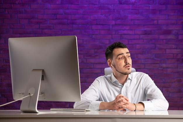 그의 작업 장소 뒤에 앉아 이어폰을 통해 이야기 전면보기 회사원