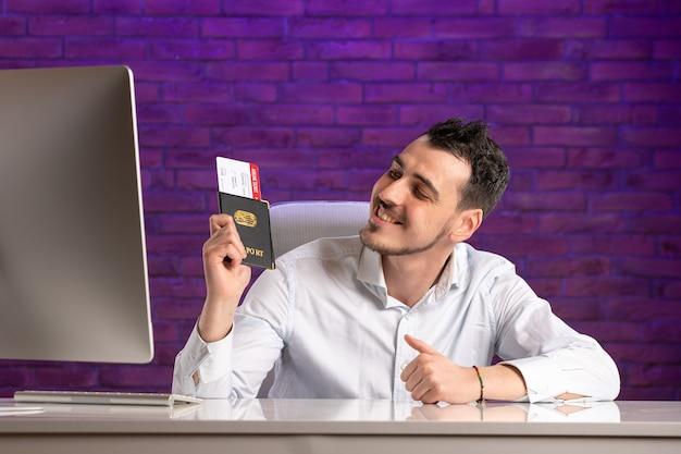 チケットとパスポートを持って彼の職場の後ろに座っている正面のサラリーマン