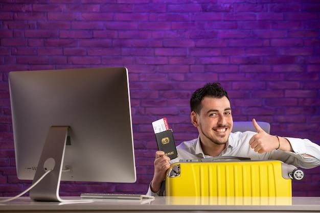 チケットのパスポートとバッグを持って彼の職場の後ろに座っている正面のサラリーマン