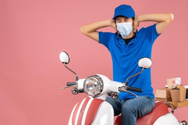 Vista frontale del ragazzo delle consegne emotivo nervoso in maschera medica che indossa un cappello seduto su uno scooter su sfondo color pesca pastello