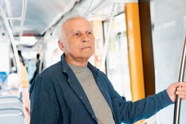 Vista frontale dell'uomo anziano nel trasporto pubblico Foto Gratuite