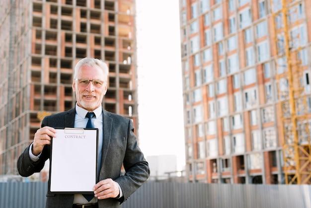Uomo anziano di vista frontale nel contratto della tenuta del vestito Foto Gratuite