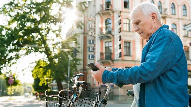 Vista frontale dell'uomo anziano con la bicicletta