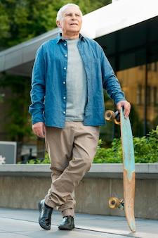 Vista frontale del vecchio con skateboard